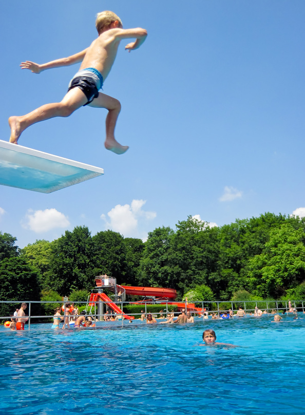 Boy is jumping from a jumping tower in an outdoor swimming pool